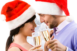 Portrait of happy couple in Santa caps with champagne flutes looking at each other