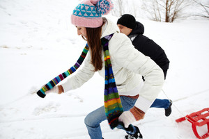 Portrait of happy couple in warm clothes running outdoors in winter