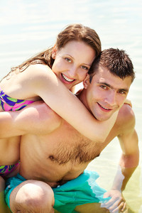 Portrait of happy couple on summer vacation looking at camera