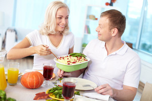 Portrait of happy couple sitting at festive table and going to eat mashed potatoes