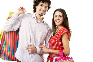 Portrait of happy couple with bags in hands on white background