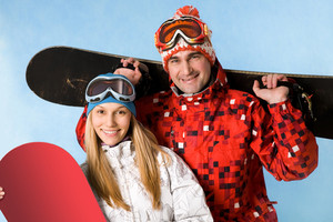 Portrait of happy couple with snowboards in hands looking at camera on blue background