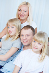 Portrait of happy couple with twin daughters smiling at camera