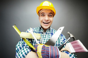 Portrait of happy craftsman with different tools in hands