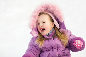 Portrait of happy cute child in winter clothes laughing and having fun