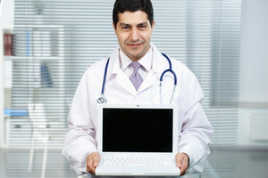 Portrait of happy doctor with open laptop looking at camera