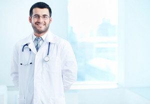 Portrait of happy doctor with stethoscope looking at camera