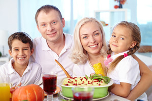 Portrait of happy family having dinner at home