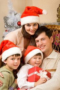 Portrait of happy family in Santa caps at home