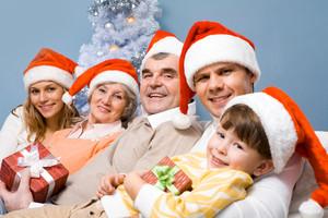 Portrait of happy family in Santa caps on Christmas Eve