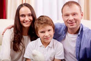 Portrait of happy family of three looking at camera at home