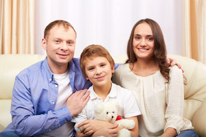 Portrait of happy family of three sitting at home and looking at camera
