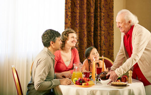 Portrait of happy family sitting at festive table and looking at senior man during Thanksgiving dinner
