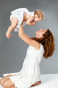 Portrait of happy female playing with her baby