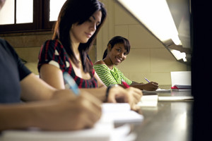 Portrait of happy female student writing and preparing test, pretty black girl smiling at camera in college library