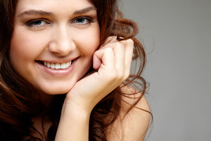 Portrait of happy female touching her face and laughing