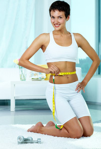 Portrait of happy fit female measuring her waist after workout