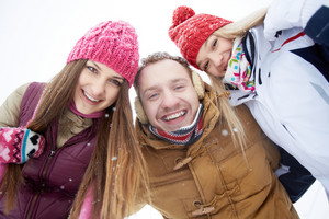 Portrait of happy friends looking at camera in winter