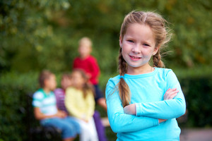 Portrait of happy girl crossing arms and looking at camera with her friends on background