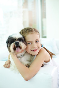 Portrait of happy girl embracing shih-tzu dog and looking at camera