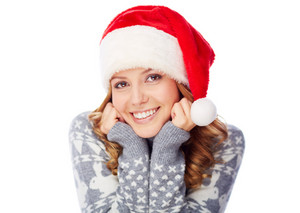 Portrait of happy girl in grey sweater and Santa cap posing for camera