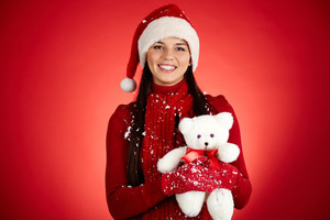 Portrait of happy girl in Santa cap holding white teddy bear and looking at camera