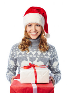 Portrait of happy girl in sweater and Santa cap holding giftboxes and looking at camera
