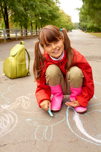 Portrait of happy girl looking at camera while drawing with chalk on road on autumnal day
