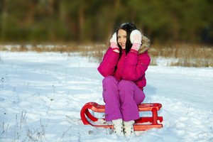 Portrait of happy girl sitting on sledge and looking at camera