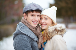 Portrait of happy guy and his girlfriend looking at camera outside