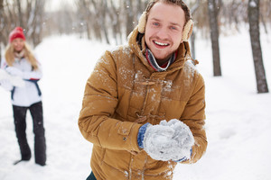 Portrait of happy guy in winterwear looking at camera on background of his girlfriend outside