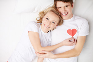 Portrait of happy guy looking at camera with his girlfriend near by holding red heart by his chest