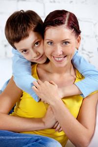 Portrait of happy kid embracing his mother