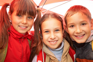 Portrait of happy kids looking at camera while under umbrella outside