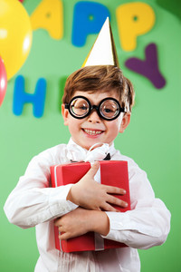 Portrait of happy lad in funny eyeglasses on birthday party with present