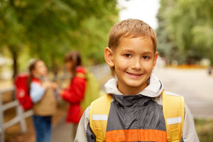 Portrait of happy lad with rucksack on back looking at camera outside