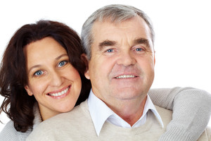 Portrait of happy mature couple looking at camera while woman embracing man