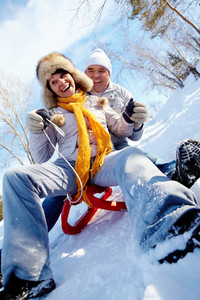 Portrait of happy mature couple riding on sledge in winter