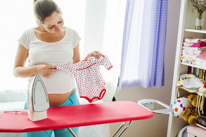 Portrait of happy pregnant woman ironing her future baby's clothes
