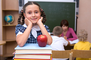 Portrait of happy schoolgirl looking at camera with pile of books and red apple near by