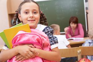 Portrait of happy schoolgirl with rucksack looking at camera
