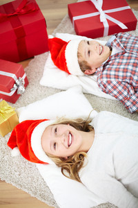 Portrait of happy siblings in Santa caps lying on pillows with giftboxes near by