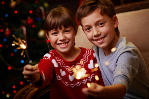 Portrait of happy siblings with Bengal lights celebrating Christmas