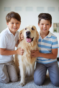 Portrait of happy siblings with pet looking at camera