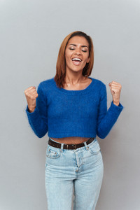 Portrait of happy smiling african woman in sweater and jeans with eyes closed. Front view. Isolated gray background