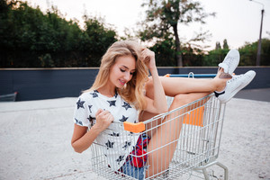 Portrait of happy smiling blonde woman having fun alone in shopping trolley