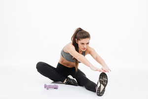 Portrait of happy sports woman stretching legs on the floor isolated on a white background