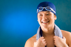 Portrait of happy sportsman in swimming cap and goggles over blue background