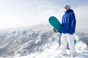 Portrait of happy sportsman with snowboard standing on top of mount