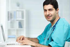 Portrait of happy surgeon typing on laptop and looking at camera